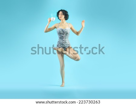 Young attractive woman in yoga asana with a cup of some hot drink. Isolated