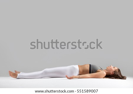 Young attractive woman practicing yoga, lying in Dead Body, Corpse exercise, Savasana pose, working out wearing sportswear, indoor full length, isolated against grey studio background