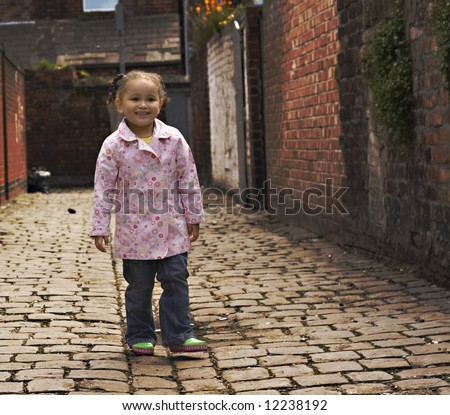 Young baby girl playing on cobble stoned alley