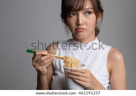 Young beautiful asian girl eating instant noodle using chopsticks.