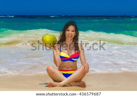 Young beautiful Asian girl  with long black hair in bikini, drinking coconut water on the beach of a tropical island. Summer vacation concept.