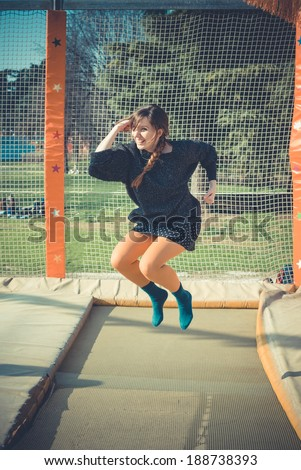 young beautiful blonde hipster woman jumping on trampoline outdoors