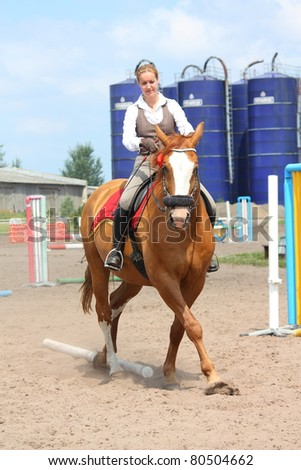Young beautiful blonde woman doing half-pass on chestnut danish warmblood horse
