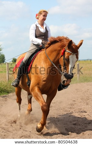 Young beautiful blonde woman trotting on chestnut danish warmblood horse