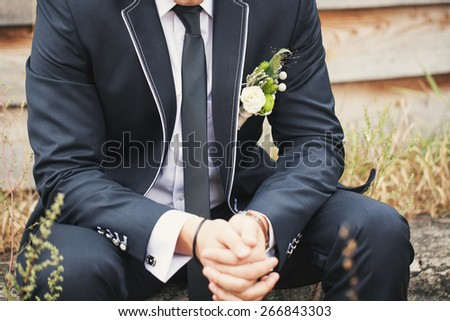 Young beautiful bride in a wedding suit and buttonhole on the nature near the wooden house
