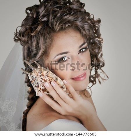 Young beautiful bride woman in wedding dress and luxury coiffure with cockleshell