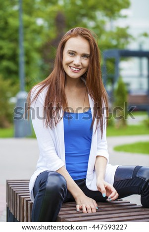 Young beautiful brunette woman sitting on a bench in the summer park