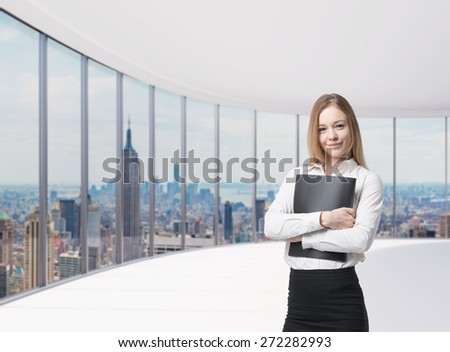 Young beautiful business lady is holding a black document case. New York panoramic office. A concept of legal services.