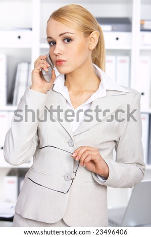 Young beautiful business woman is using mobile phone