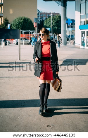 Young beautiful caucasian red dressed woman walking outdoor in the city, holding smart phone and a bag, overlooking - communication, technology concept