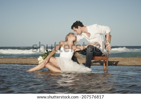 Young beautiful couple flirting at water's edge with white roses
