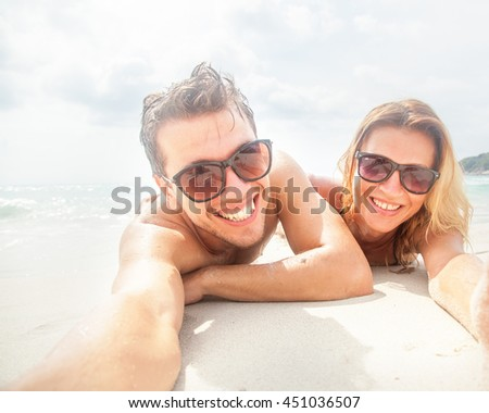 Young couple standing embracing on beach stock photo for Tropical vacations for couples