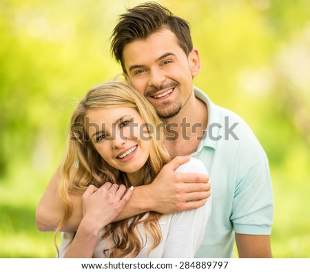 Young beautiful couple sitting on the lawn in summer park. Man hugging woman.