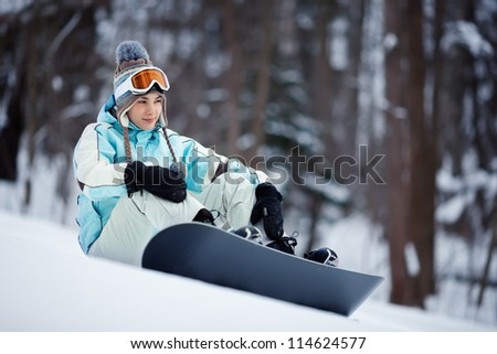 Young beautiful female snowboarder resting on ski slope, she's looking away and smiling