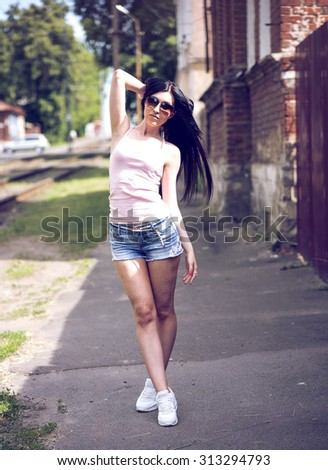Young beautiful girl posing in a fashion city in short denim shorts, blouse and sunglasses sexy woman
