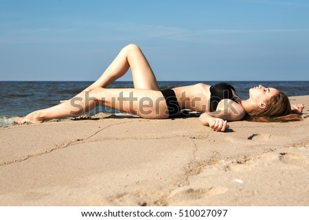 Young beautiful girl posing on the beach, wearing fashionable swimsuit.