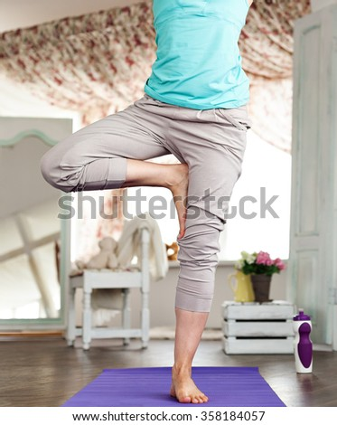 Young beautiful girl practicing yoga at home. yoga studio in the daytime. Purple yoga mat.