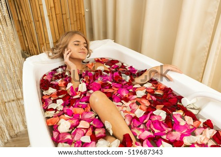 Young beautiful girl receives taking bath with rose petals in spa