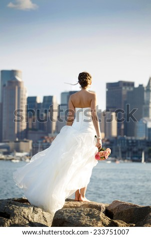 Young beautiful girl stands on the rocks over Boston downtown background