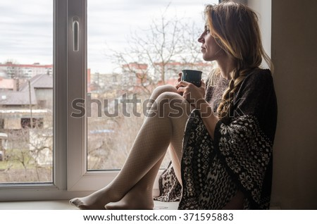 Young beautiful girl student sitting on a window sill at the window overlooking the city and drinking hot coffee from a mug