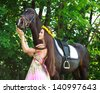 Young beautiful girl with a horse in green forest - stock photo