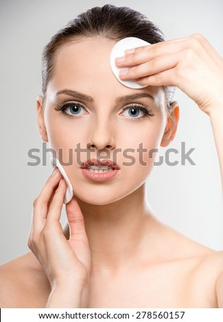 Young beautiful girl with cotton swab cleaning her face. Skin care concept.