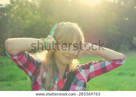 young beautiful girl with headphones on ears listening music in smartphone on the meadow in vintage style