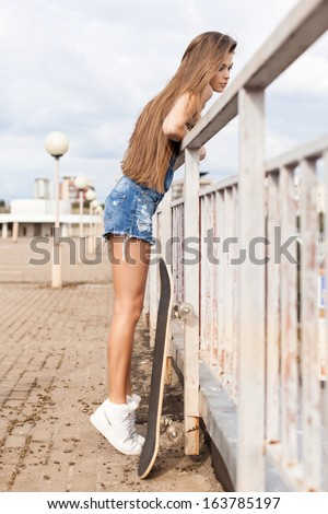 Young beautiful girl with long legs and silky hair in denim short