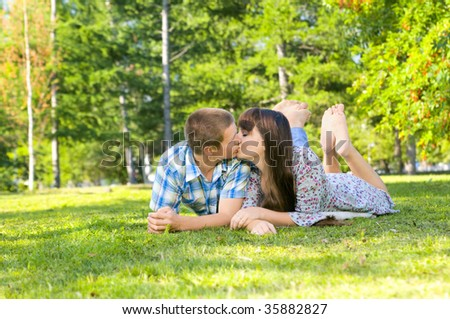 Young beautiful guy and the girl, sits on a lawn, kisses .