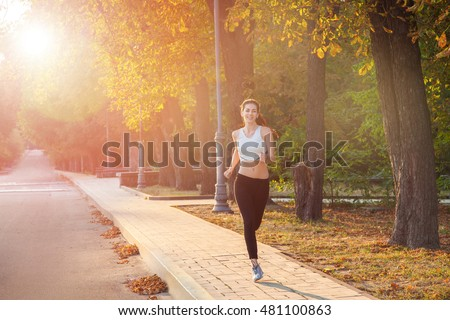 young beautiful happy and sexy runner girl with nice body in the autumnal colored park. with sun on backlight is looking at camera with happiness and smile with white sport suit.