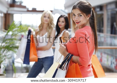 Young beautiful happy women with shopping bags and credit card in mall