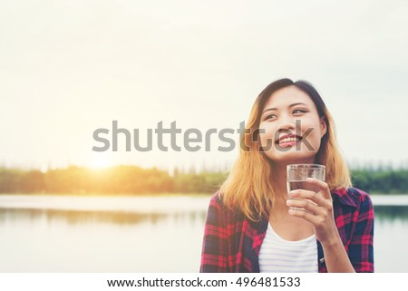 Young beautiful hipster woman Holding water standing on pier, relaxing enjoy with nature.