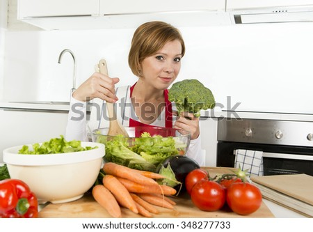 young beautiful home cook woman at modern domestic kitchen mixing  vegetable salad bowl smiling happy and satisfied in healthy eating veggie nutrition and lifestyle concept