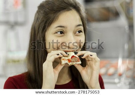 Young beautiful lady eating a hotdog sandwich.