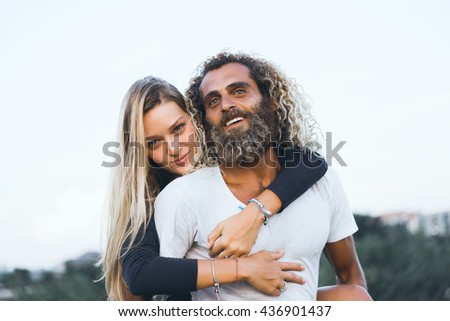 Young beautiful loving couple, a blonde Girl and laughs together with her beautiful Bearded man, Crazy guys, hipsters, Fun and creative, outdoor portrait, close up