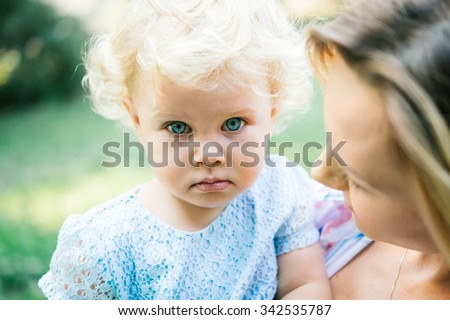 Young beautiful mother with her toddler blonde daughter during a walk outdoors
