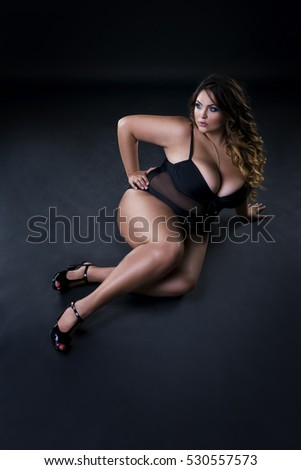Young beautiful plus size model in underwear, xxl woman on black background, full length portrait
