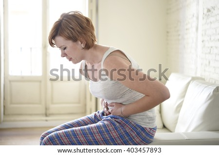 young beautiful red hair woman holding hurting belly suffering stomach cramp and period pain sitting on home couch in painful face expression female menstruation concept