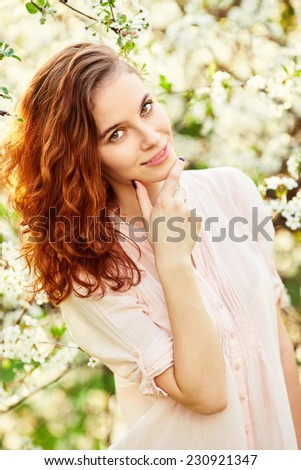 Young beautiful red-haired woman in blooming garden