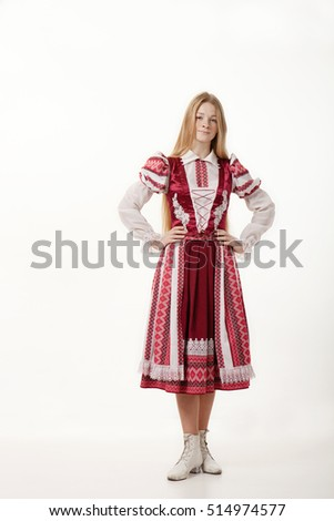 Young beautiful redhead woman dancer in traditional folk costume posing isolated on white background