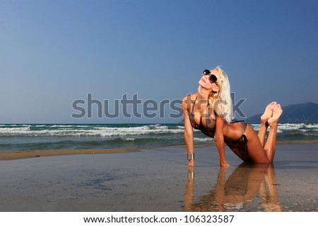 Young beautiful sexy blond woman on a beach with water reflection