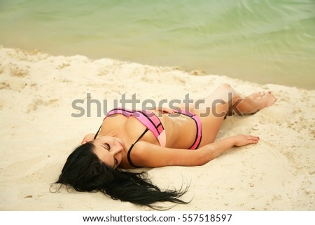young beautiful sexy girl in swimwear lying on a sandy beach