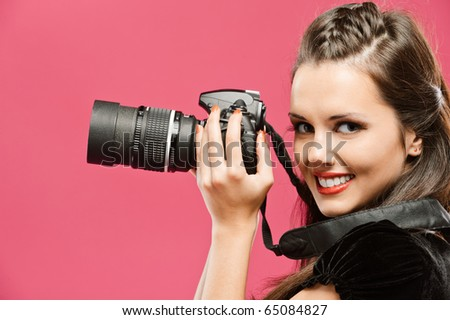 Young beautiful smiling woman-photographer hold in hands DSLR, going to make picture, on red background.