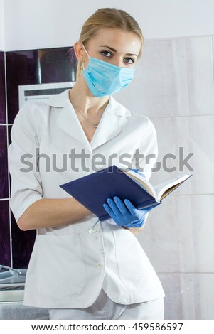 Young beautiful woman dentist. With a notebook and pen