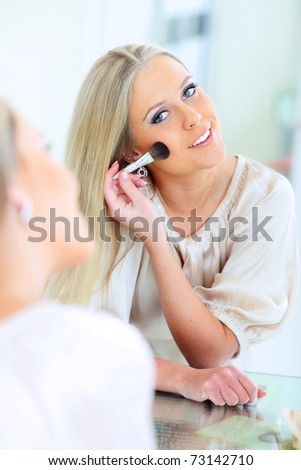 Young beautiful woman doing makeup and looking to herself at the mirror