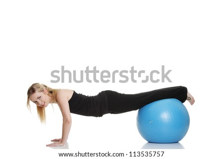 Young beautiful woman during fitness time and exercising with blue ball, isolated on white background