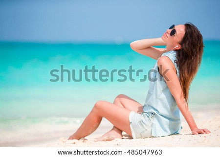Young beautiful woman enjoying the music on the beach