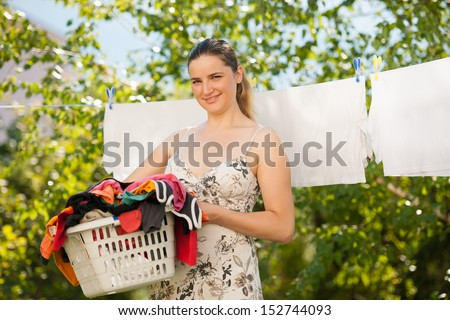 Young beautiful woman hanging laundry outdoor