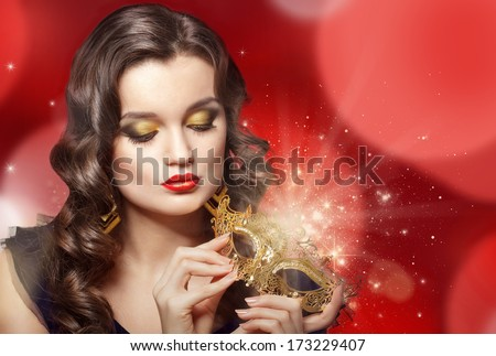 Young beautiful woman holding golden carnival mask.