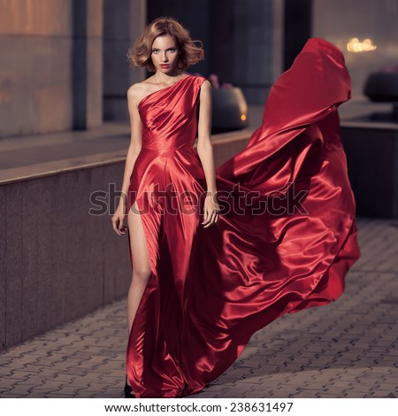 Young Beautiful Woman In Fluttering Red Dress. City Background.